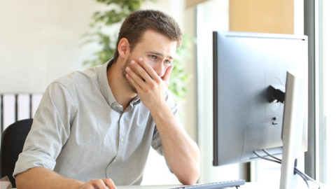 Man sitting at computer_shutterstock_453831763